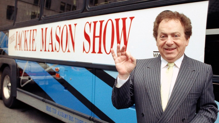 Actor/comedian Jackie Mason in 1992 standing beside a bus displaying a sign advertising his TV show, 1992. (AP Photo)